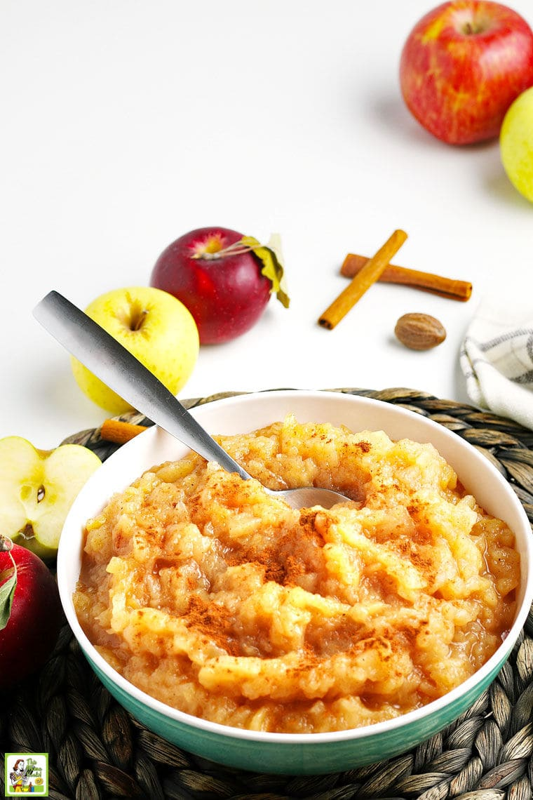Closeup of a bowl of homemade apple with a serving sppon with apples, cinnamon, and nutmeg and a dishtowel in the background.
