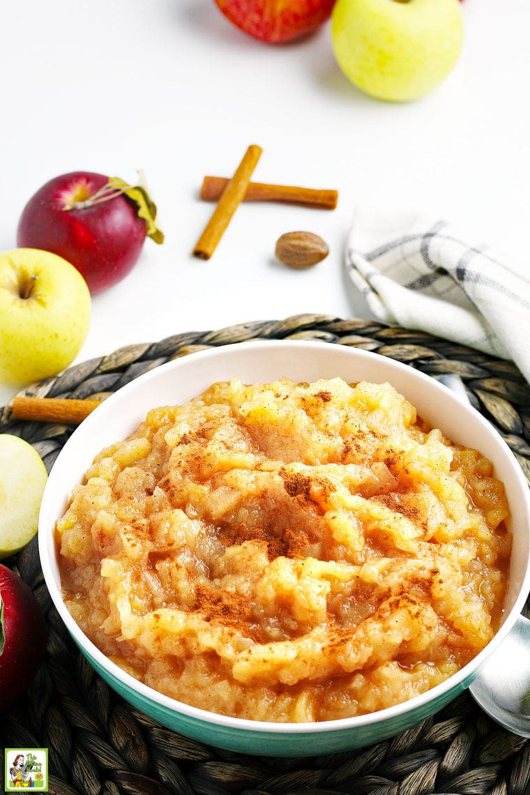 A large bowl of applesauce with a black and white dishtowel, apples, and cinnamon sticks.