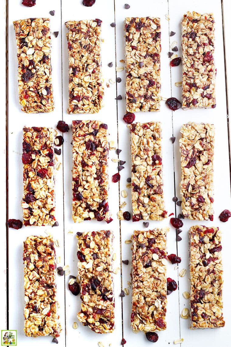 Homemade granola bars made with chocolate chips, oatmeal, and dried cranberries on a white wooden board.