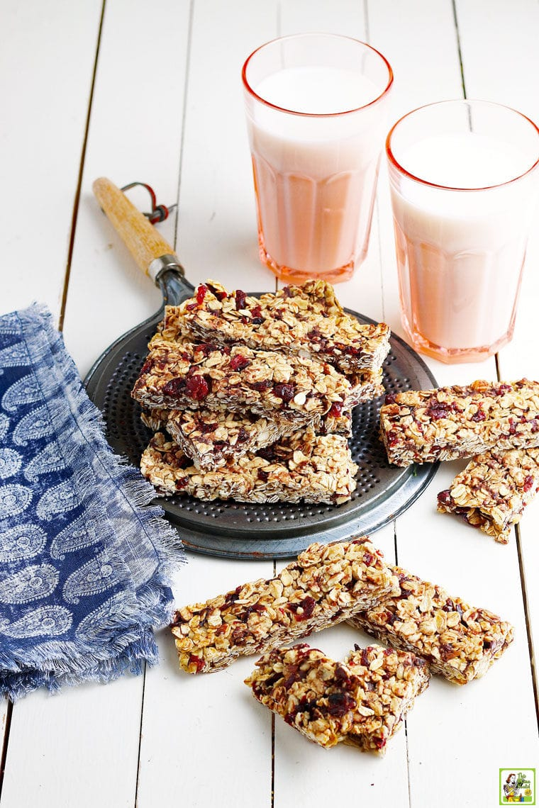 A stack of granola bars with chocolate chips and dried cranberries on a metal trivet with a blue and white napkin and two pink glasses of milk on a white wooden countertop.