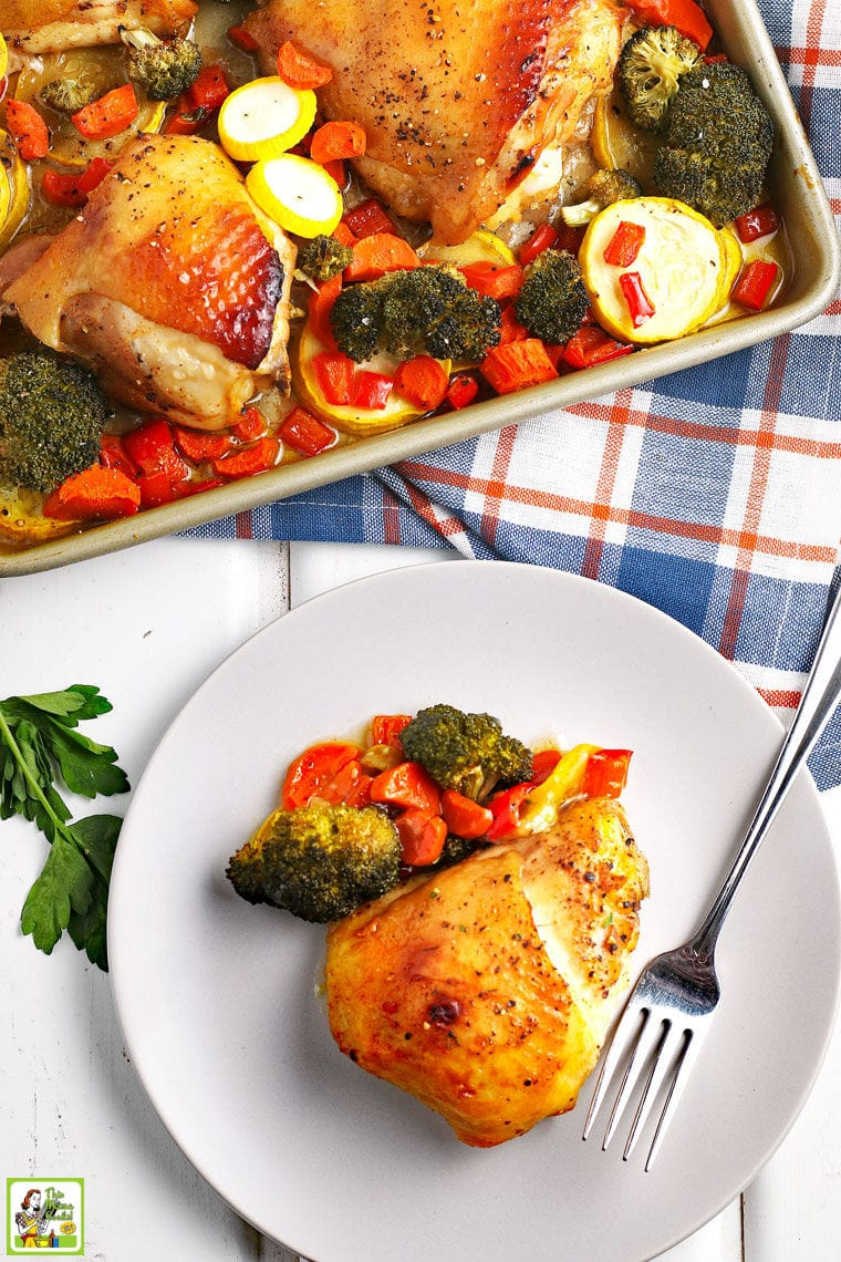 Baked chicken thigh and roasted vegetables on a white plate with a fork, plaid napkin, and a baking sheet with more chicken and roasted vegetables.