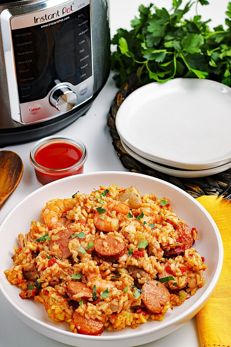 A large white bowl of jambalaya with shrimp, chicken, and sausage, a wooden spoon, a yellow napkin, ramekin of hot sauce, Instant Pot pressure cooker, a stack of white plates, and a bunch of fresh parsley.
