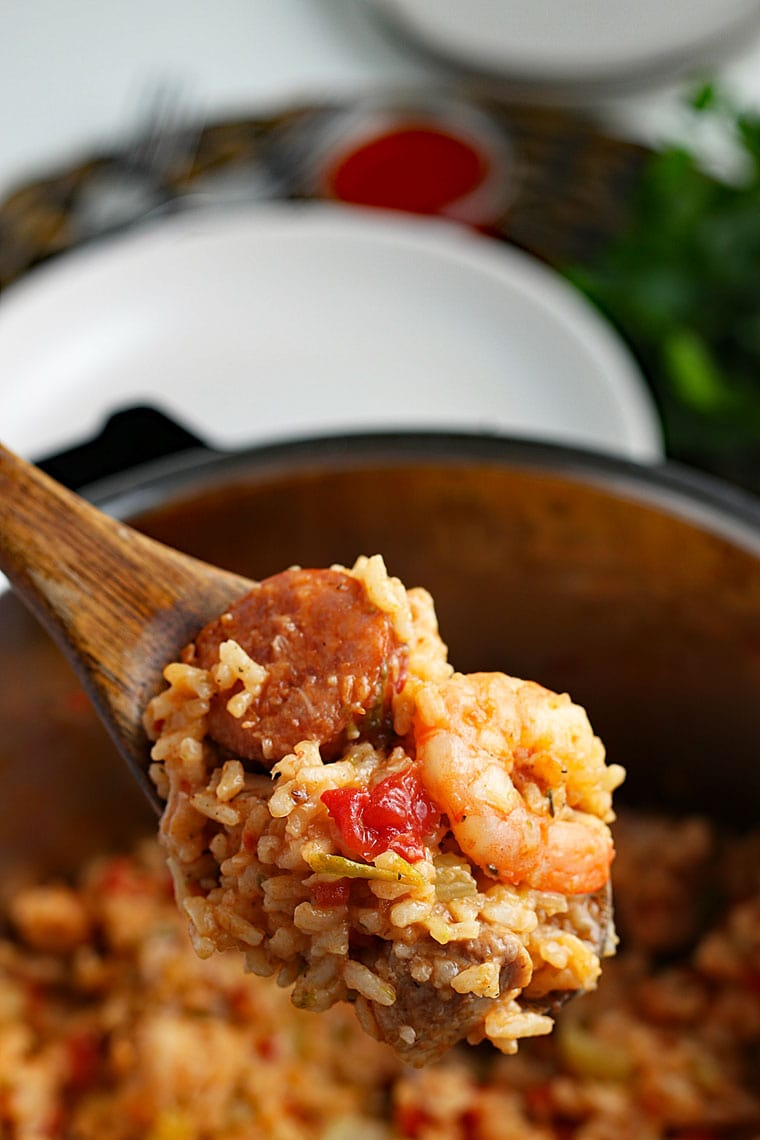 A wooden spoon filled with jambalaya with rice, shrimp, and sausage above a pressure cooker pot of jambalaya with a white plate and ramekin of hot sauce in the background.