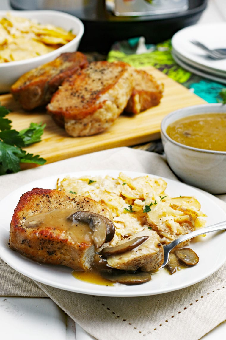 Pork chops and scallop potatoes on a white plate with fork on a linen napkin with a bowl of gravy with pork chops on a wooden cutting board in the background.