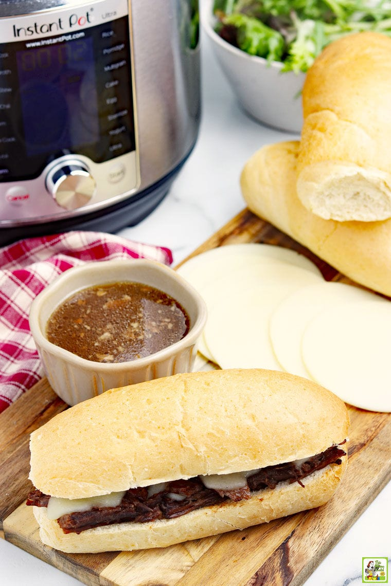 Closeup of a French dip sandwich with au jus, red and white napkin, slices of cheese and bread rolls, and an Instant Pot  and a bowl of salad in the background.