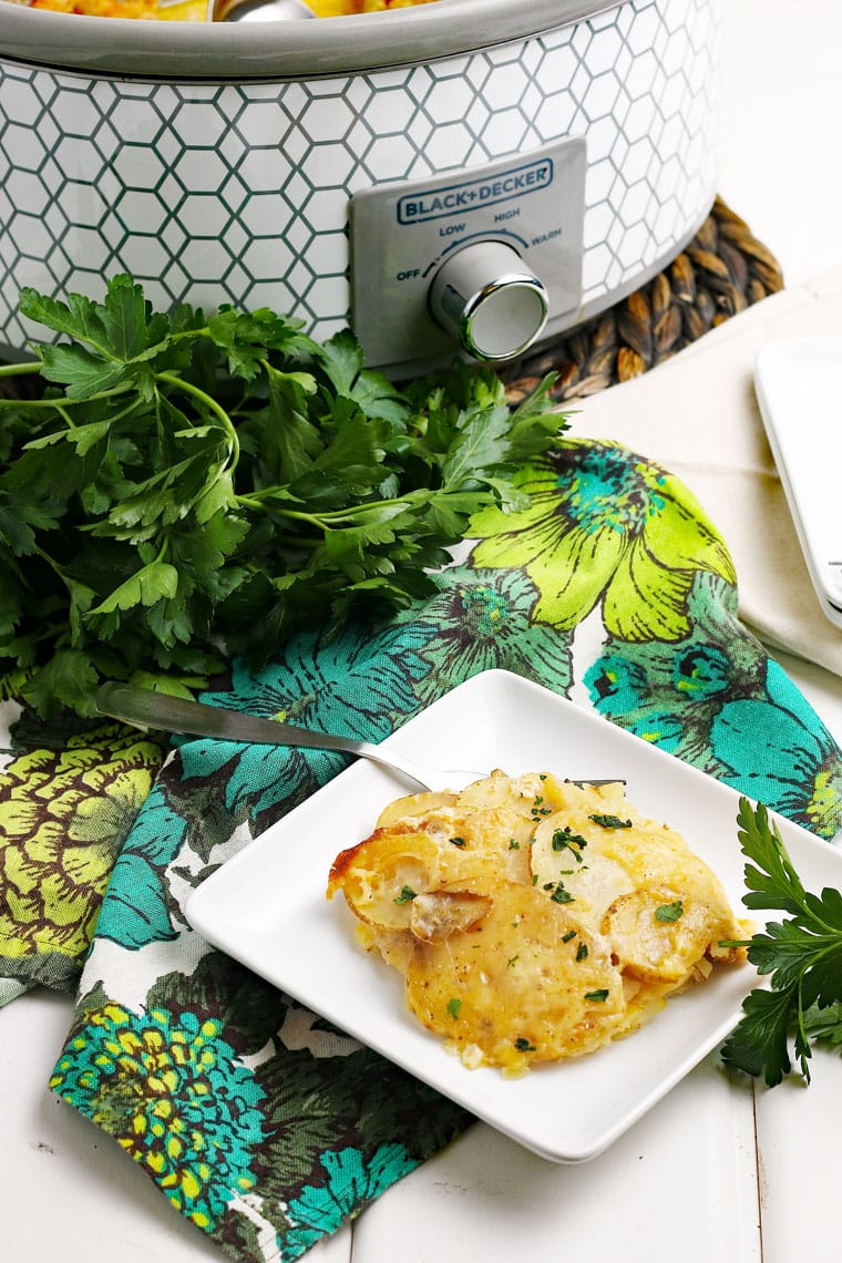 A crock-pot and white square plate with fork of scalloped potato with floral napkin and a bunch of parsley.