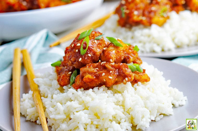 A plate of General Tso chicken served on rice with chopsticks.