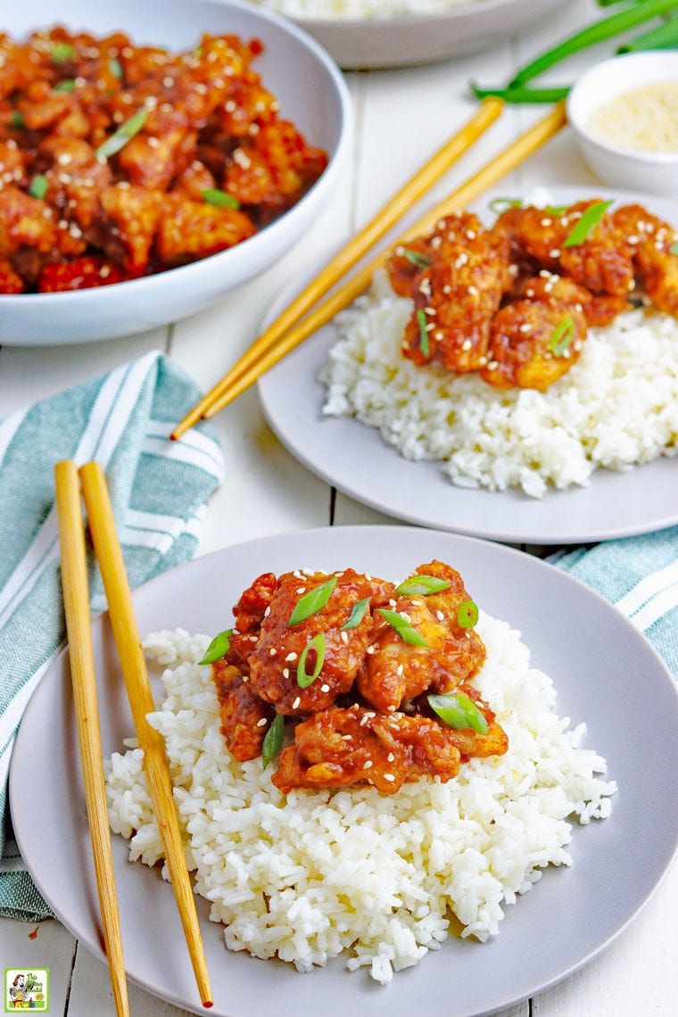 Plates of General Tso's chicken served on rice with chopsticks and a large bowl of cooked chicken in the background.