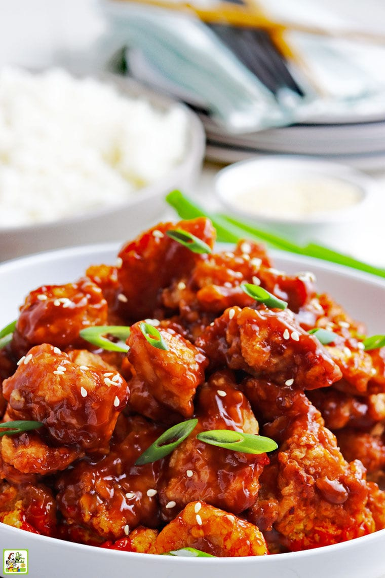 Closeup of a bowl of General Tso's chicken stir fry with sesame seeds and sliced green onions with a bowl of steamed rice in the background.
