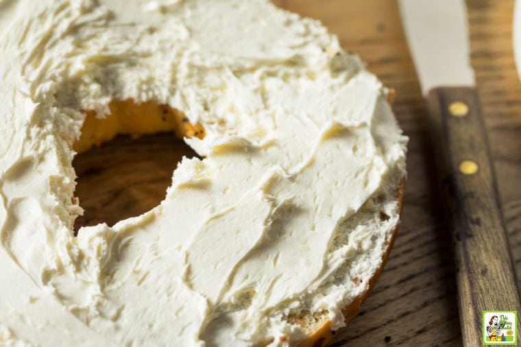 Closeup of a cream cheese covered bagel and a knife.