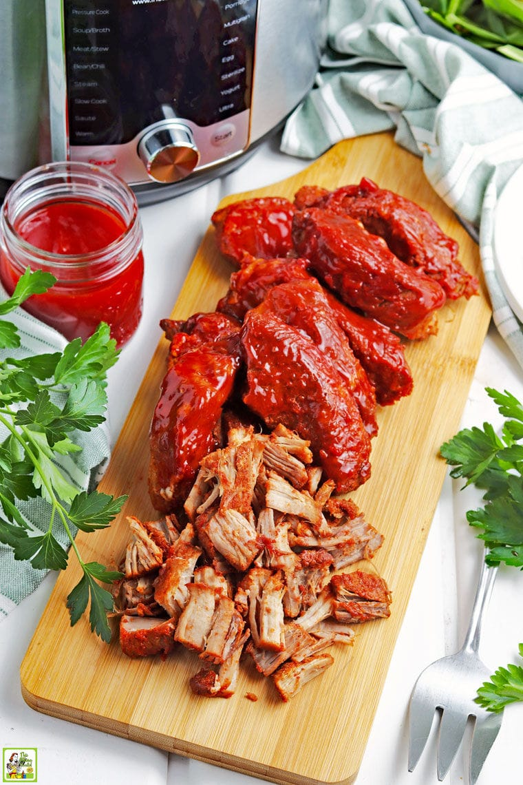 Instant Pot barbecue country style ribs wooden cutting board, a jar of BBQ sauce, and a serving fork.
