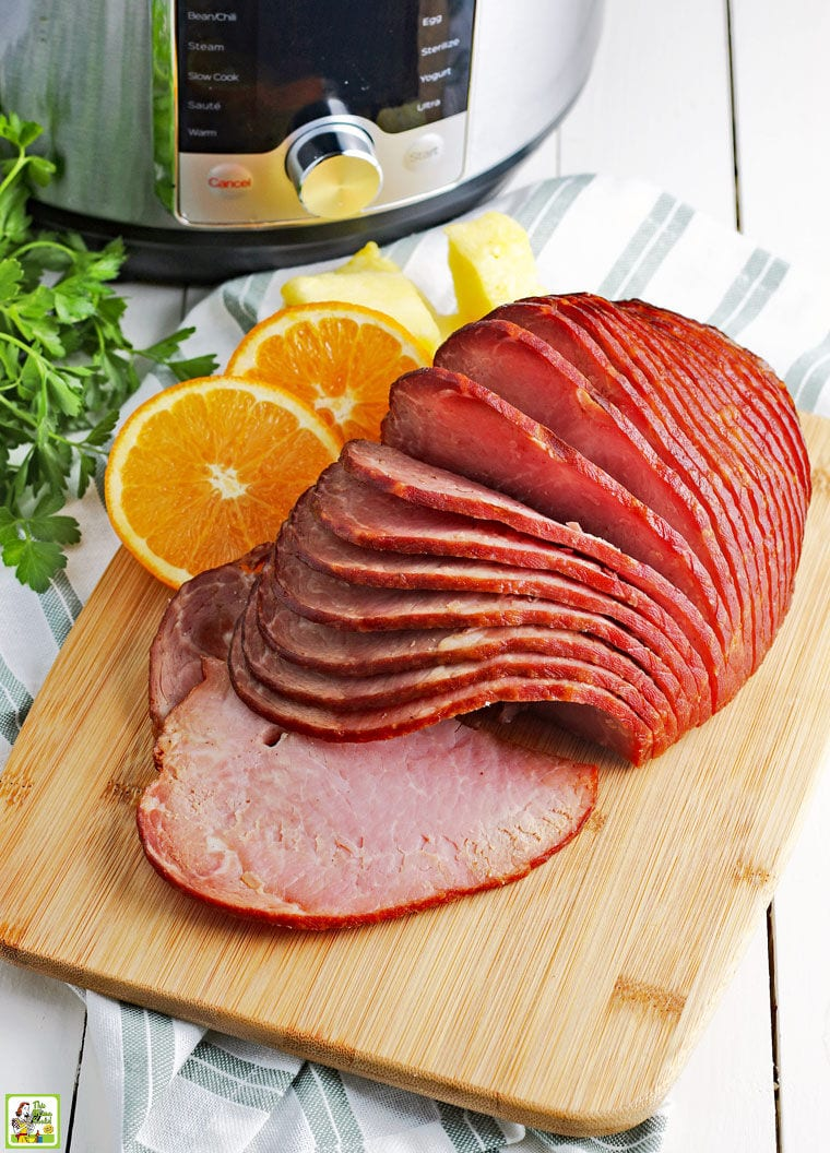 Spiral Instant Pot Ham on a wooden cutting board with orange slices with an instant pot pressure cooker.