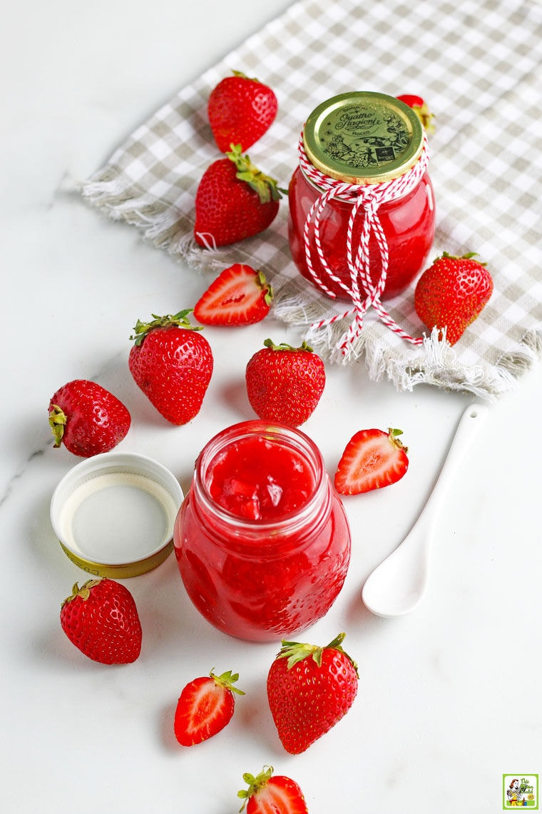Overhead shot of glass jars of strawberry sauce with a white spoon, gray napkin, and sliced and whole strawberries.