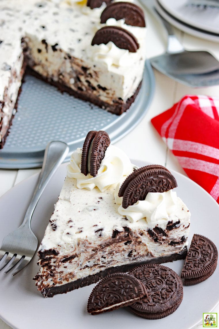 A slice of cheesecake with Oreos on a plate with a whole cheesecake in the background.