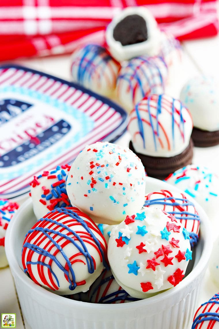 Red, white and blue Oreo balls in a bowl and with Oreos and holiday paperplates on a festive tabletop.