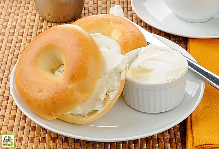 A sliced bagel with cream cheese and coffee.