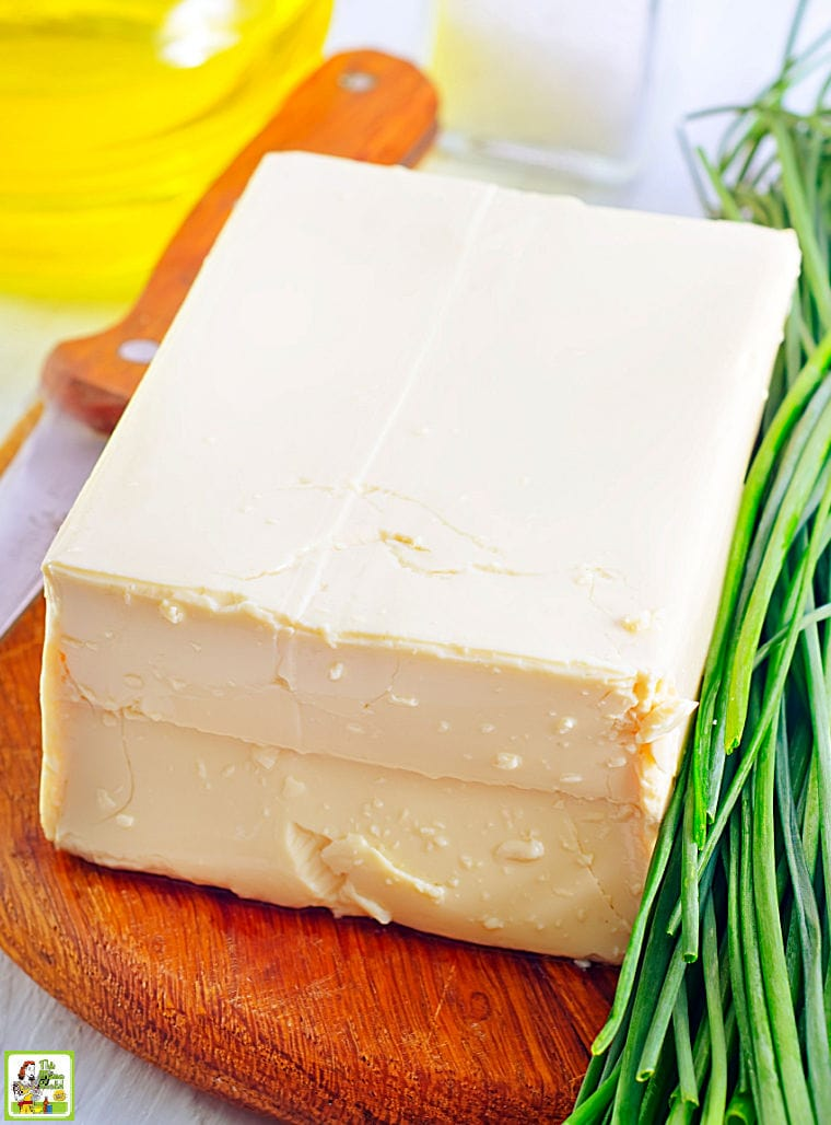 A block of tofu and chives on a wooden cutting board.