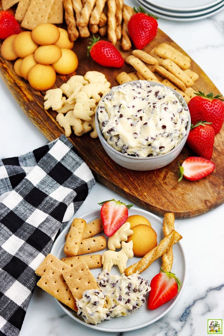 Overhead shot of a dessert board of chocolate chip cookie dough dip in a bowl and dippers of fruit, vanilla cookies, animal crackers, and cookie dough dip and dippers on a plate in the foreground.