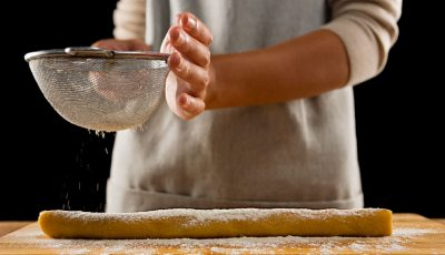 Woman sprinkling powdered sugar over baking dough.