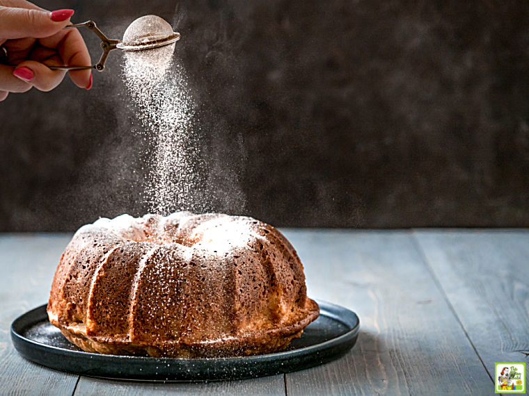 Hand sprinkling powdered sugar over a bundt cake on a dark colored plate.