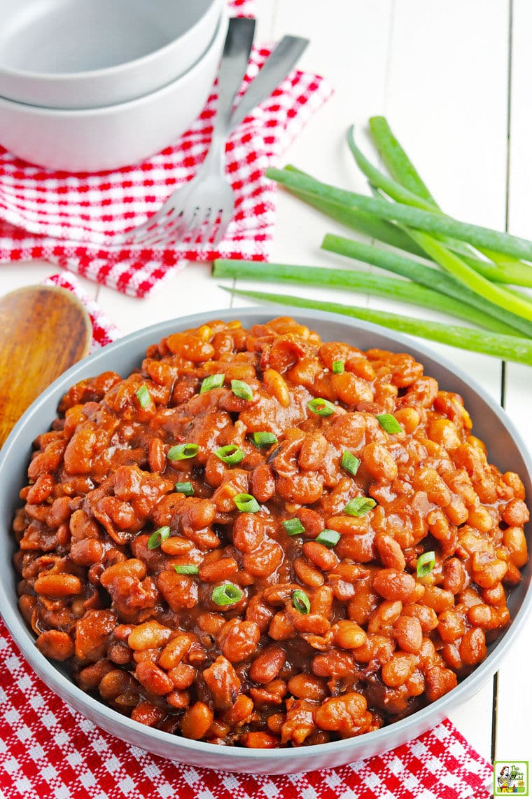 A large blue bowl of Instant Pot Baked Beans with green onions red and white checkered napkins, bowls, and forks.
