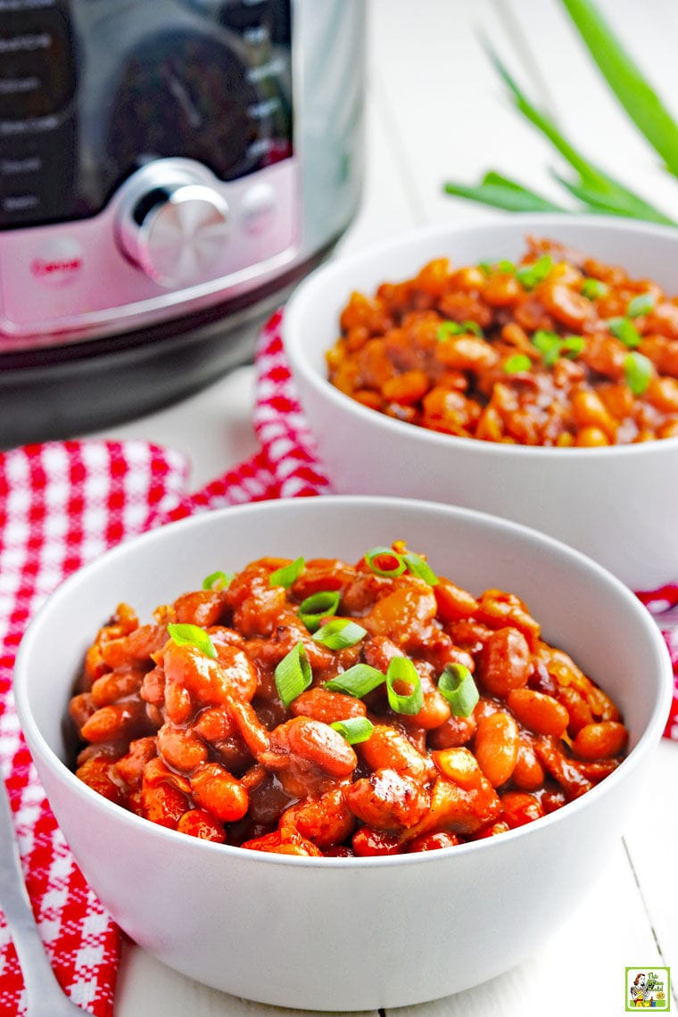 Bowls of baked beans on red and white napkins with a pressure cooker in the background.