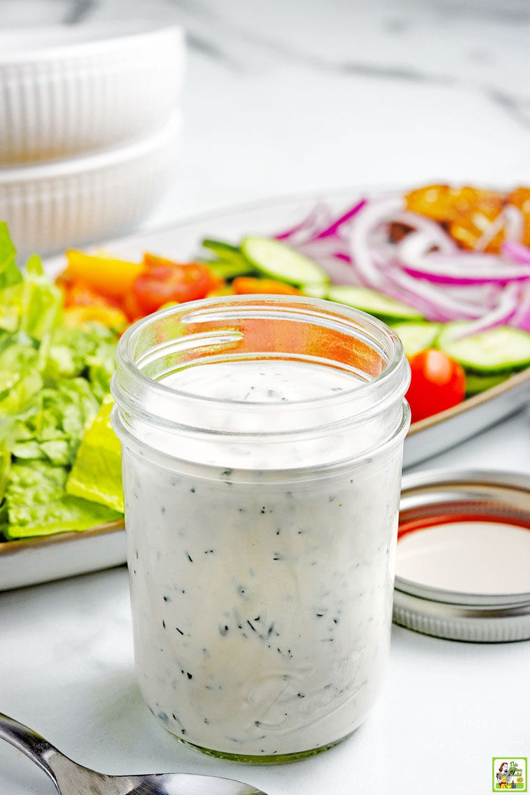 A mason jar of Low-Carb Keto Ranch Dressing with a platter of salad fixings, bowls, and a fork.