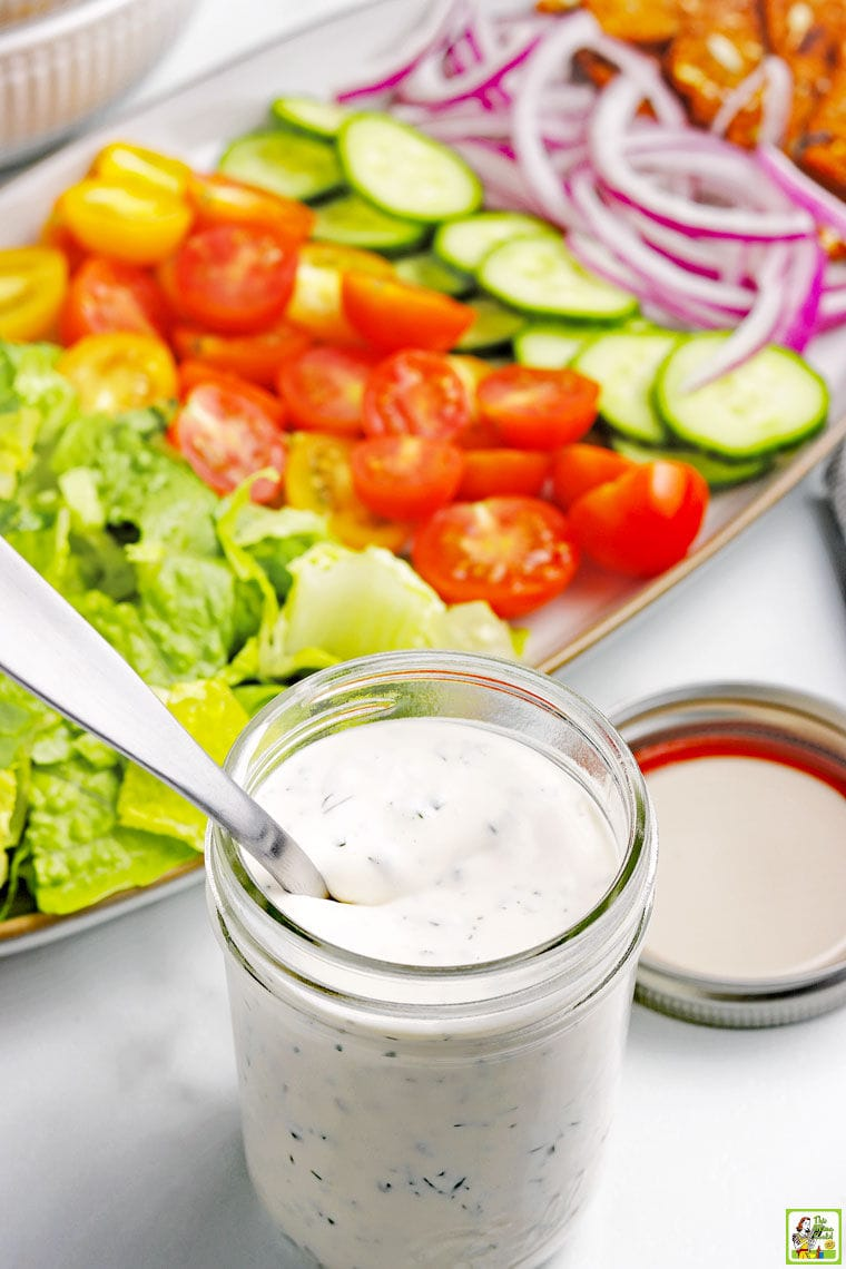 A jar of homemade ranch dressing in a mason jar with lid and spoon and a platter of salad fixings including lettuce, sliced tomatoes, cucumbers, and onions.