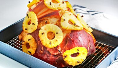 Spiral ham with cloves and pineapple rings in a baking pan.