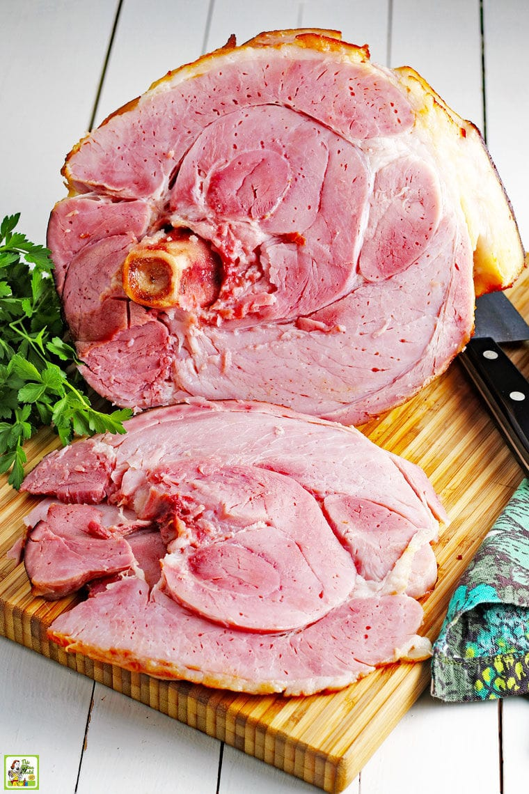 Slices of a spiral cut ham on a wooden platter with knife and green and blue napkins.