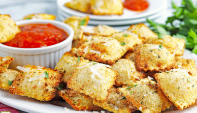 Closeup of a plate of fried air fryer ravioli and a ramekin of marinara sauce.