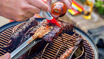 Brushing BBQ sauce on racks of pork ribs during grilling.