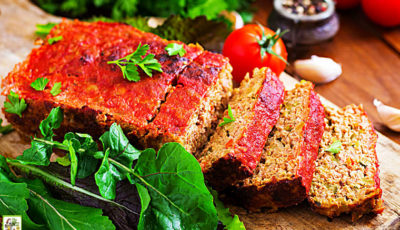 Sliced loaf of meat loaf covered in tomato sauce on a wooden cutting board with fresh herbs.